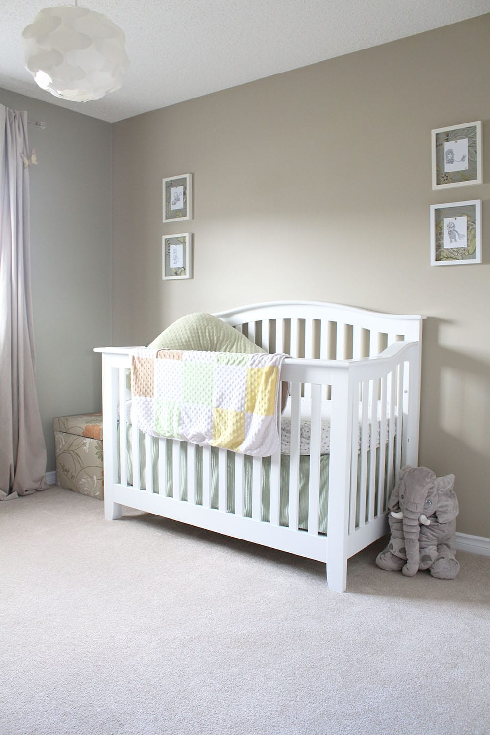 A neutral baby bedroom with a white crib and baby superhero art.