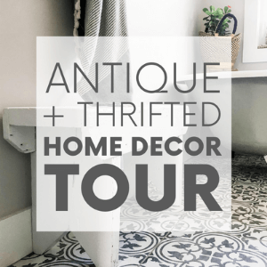 """A white and light grey bathroom with an antique clawfoot tub with the words """"antique + thrifted home decor tour."""" Click to visit post."""