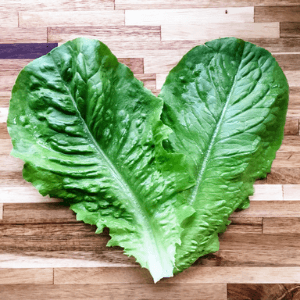 Two lettuce leaves creating a heart-shape on a wooden background.